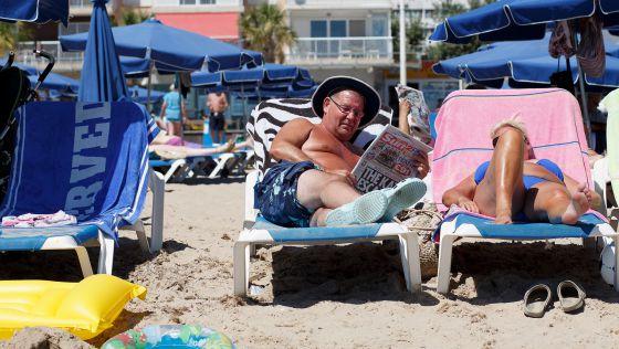 Un hombre lee un diario británico en una playa de Benidorm
