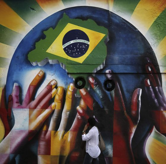 Una mujer pasea ante un mural de protestas en Sao Paulo (Brasil).