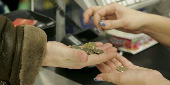 Una cajera ayuda a un cliente a contar las monedas.