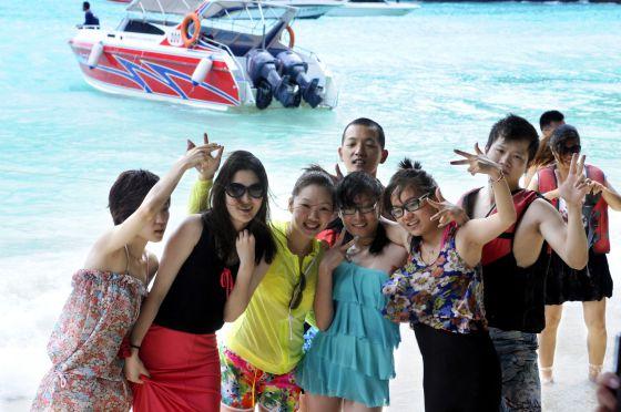 Un grupo de turistas chinos disfruta de un día de playa de Tailandia.