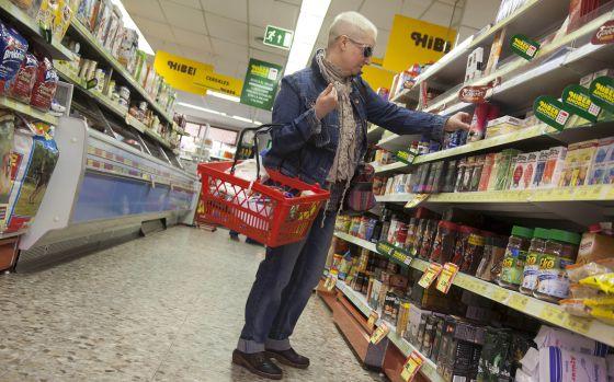Una mujer compra en un supermercado de Manzanares el Real (Madrid)