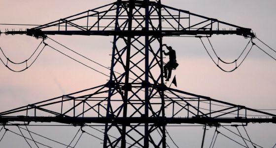 Un operario baja de una torre de luz.