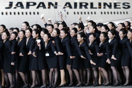Las nuevas empleadas de Japan Airlines posan frente a una aeronave de la compañía.
