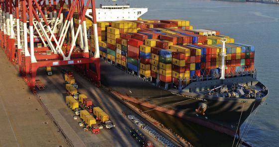 Camiones trasladan contenedores de un barco en el puerto de Qingdao (China)