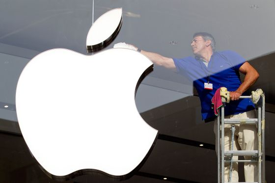 "An employee cleans the Apple symbol at one of its Spanish stores. Apple is said to have discovered ""the Holy Grail of tax avoidance."""