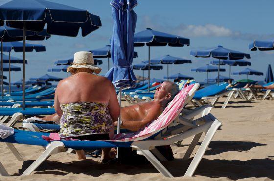 Una pareja toma el sol en la playa de Benidorm.