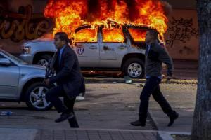 Miembros de la Policía Científica (CICPC) caminan frente a un vehículo incendiado durante una marcha convocada por la oposición, en Caracas (Venezuela).