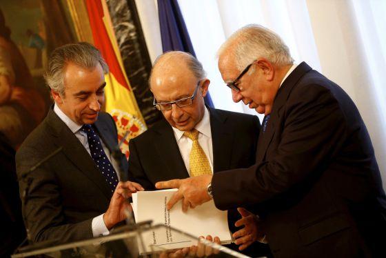 Montoro recibe el informe de manos de Lagares, derecha, junto con el Secretario de Estado Miguel Ferre.