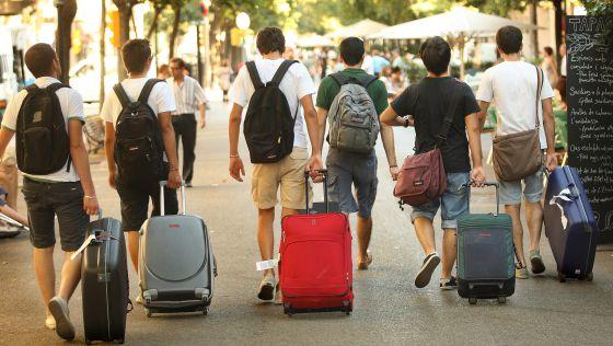 Un grupo de turistas camina con sus maletas por la Rambla de Cataluña, en Barcelona.