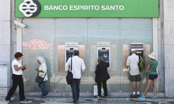 Varias personas retiran dinero de una oficina del BES en Lisboa.