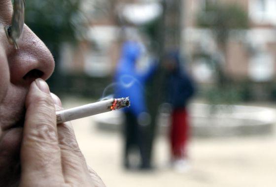 Una mujer fuma un cigarrillo en un parque