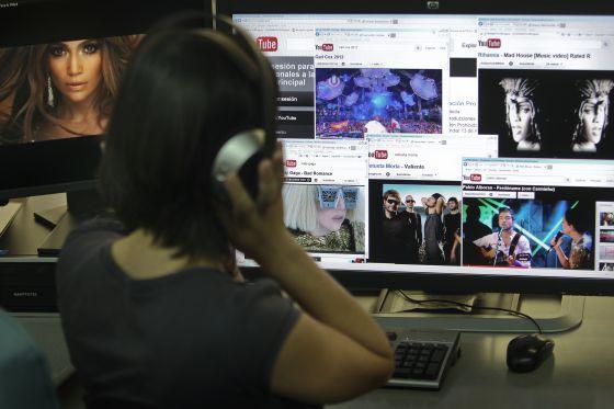 Una joven eschuca un concierto musical a través de YouTube.