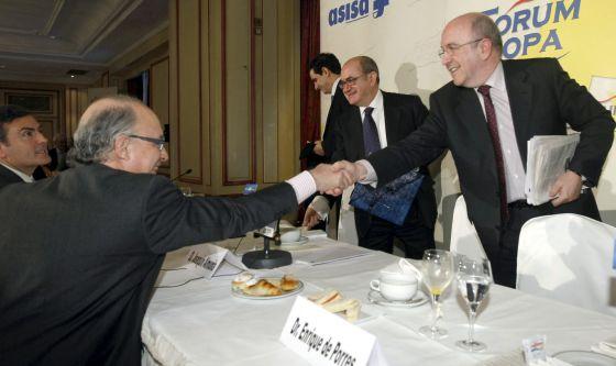 El vicepresidente de la Comisión Europea, Joaquín Almunia, a la derecha, saluda al ministro de Economía, Cristóbal Montororn