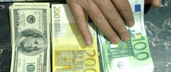 Billetes de cien y doscientos euros y de cien dolares.