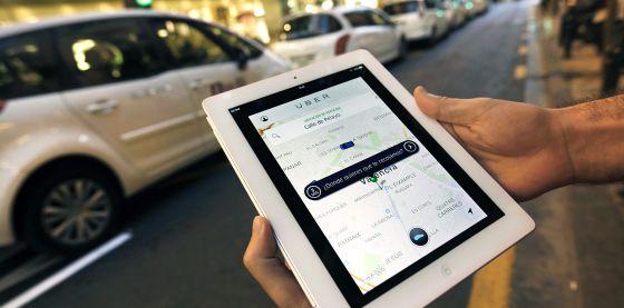 Un usuario de Uber consulta la aplicación en Valencia ante una parada de taxis.
