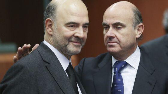 El ministro español de Economía, Luis de Guindos, saluda al comisario europeo de Asuntos Económicos, Pierre Moscovici.