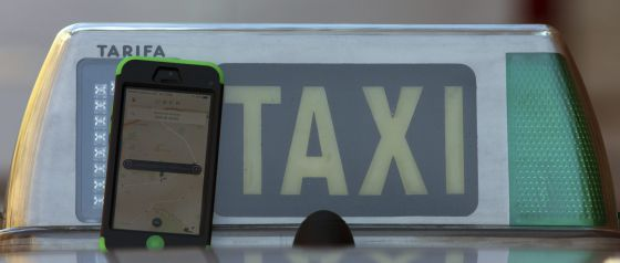 Un móvil con la aplicación de Uber junto a un taxi, esta semana en Madrid.