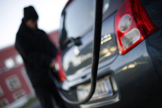 Un hombre llena el depósito de su coche.