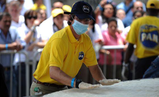 El presidente de Polar, Lorenzo Mendoza, ayuda a preparar una arepa gigante en un acto celebrado en Caracas en 2011.
