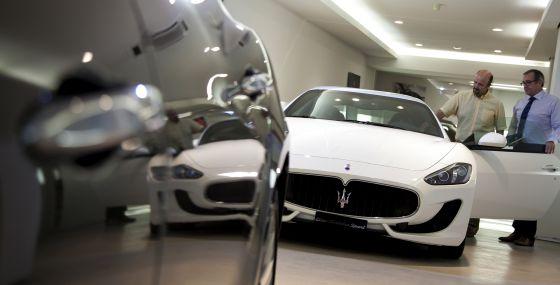 Un vendedor (izquierda) muestra un Maserati a un posible comprador en un concesionario