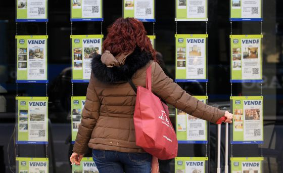 Una mujer examina los anuncios de venta de pisos en una oficina inmobiliaria de Madrid.
