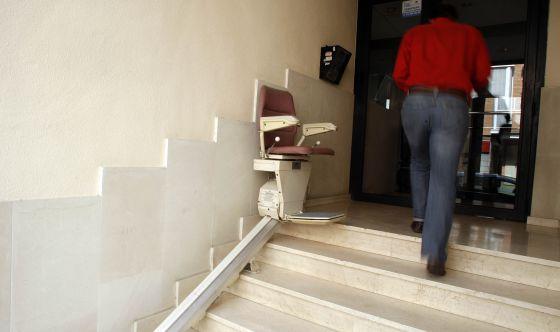 Silla mecánica para salvar las escaleras instalada en el acceso a una finca en Madrid.