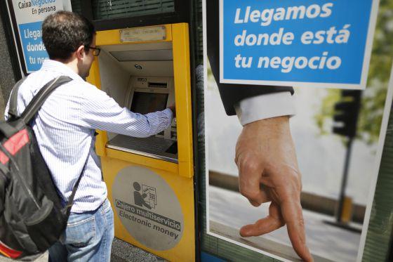 Un ciudadano utiliza un cajero automático de CaixaBank en Madrid