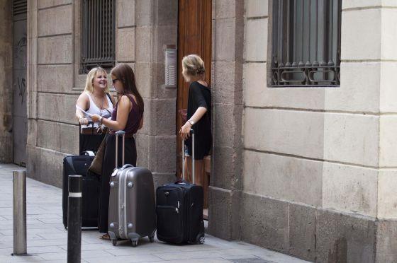 Un grupo de turistas esperan delante de un piso de alquiler en Barcelona