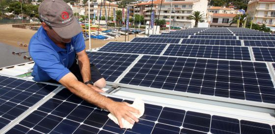 A worker installs solar panels at the Club Nautico de L'Estartit (Girona).