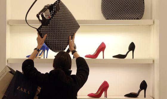 Una mujer mira un bolso en una tienda de Zara