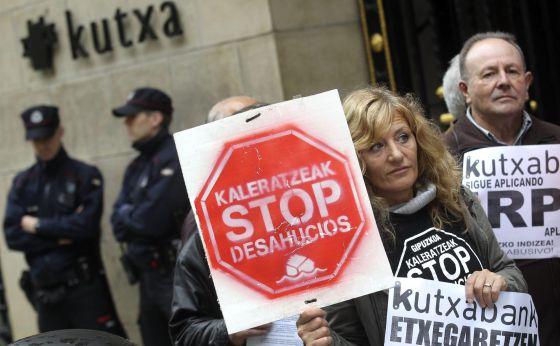 Miembros de Kaleratzeak Stop Desahucios e IRPH-STOP de Gipuzkoa participan en una concentración frente a la sede de Kutxanank en San Sebastián.