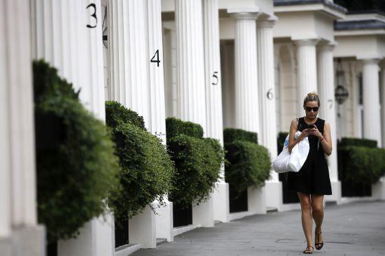 Una mujer camina por una zona residencial de lujo en Londres.