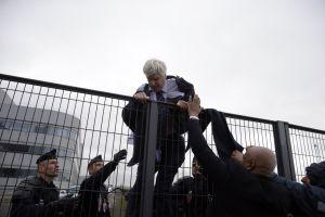 Pierre Plissonnier, con el traje y la camisa rasgados, trata de saltar una valla con ayuda de los agentes de seguridad después de que cientos de trabajadores tomasen la sede de Air France por el plan de ajuste.