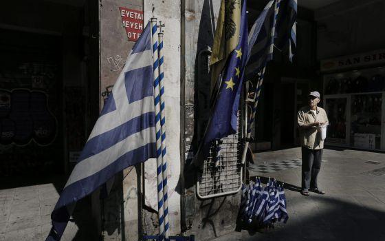 Un anciano ante una tienda que vende banderas griegas y de la UE en el centro de Atenas.