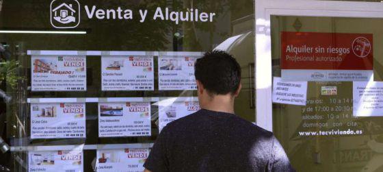 Escaparate de una inmobiliaria en Madrid con anuncios de pisos en venta.