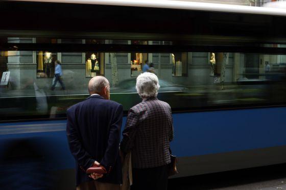 Una pareja de jubilados mira un autobús pasar en una calle de Madrid