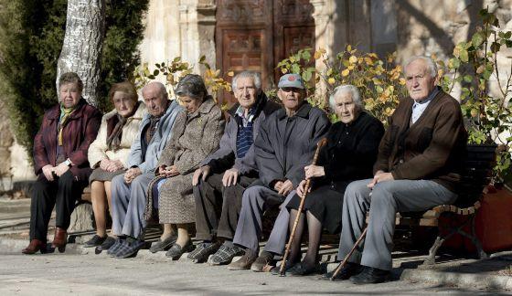 Varios ancianos sentados en unos bancos