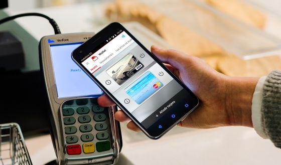 Un usuario paga con su móvil en un comercio a través de Vodafone Wallet.