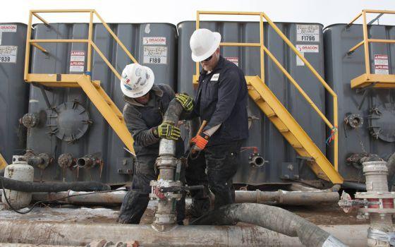 Dos trabajadores conectan mangueras a una tubería en Dakota del Norte.