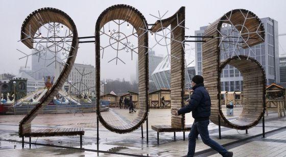 Un hombre camina frente a una decoración de año nuevo en Kiev.
