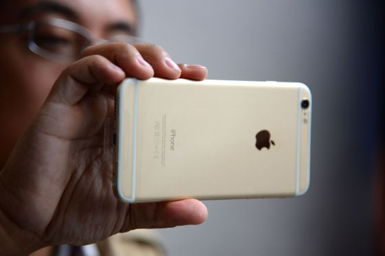 Un hombre sujeta un iPhone 6, un teléfono de Apple
