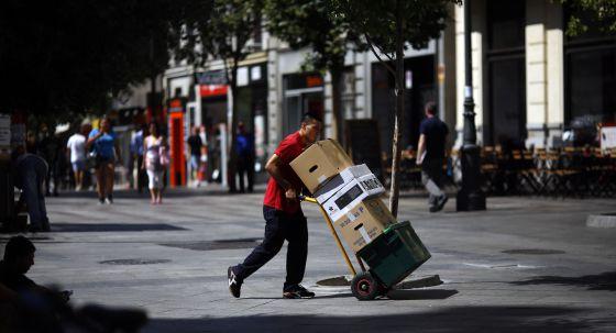 Un repartidor transporta varias cajas en el centro de Madrid