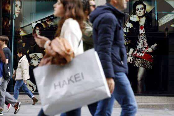 Varias personas pasan con bolsas de compras ante una de las tiendas de la céntrica calle Preciados de Madrid. EFEArchivo