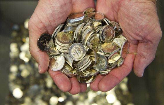 Un hombre sostiene varias monedas de euro. EFEArchivo