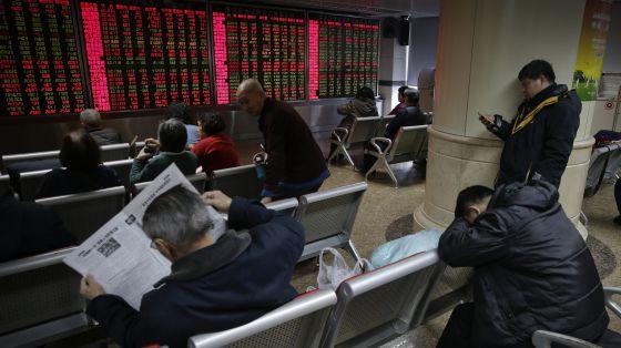 Inversores siguen la evolución de las Bolsas desde Pekín.