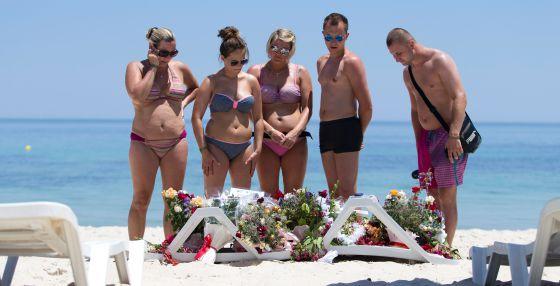 Un grupo de turistas contemplan las flores depositadas en la playa tras el ataque en junio a un hotel en Susa (Túnez).