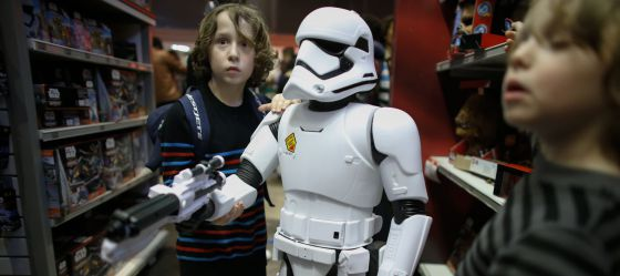 Unos niños muestran un muñeco de soldado de asalto imperial de la saga 'Star Wars' en una juguetería de Nueva York.