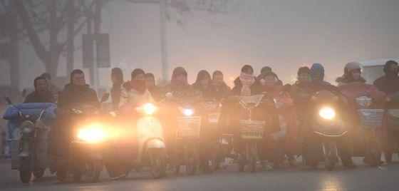 Un grupo de personas espera en un cruce en la ciudad china de Bozhou.