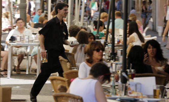 Un camarero trabaja en una terraza de verano.