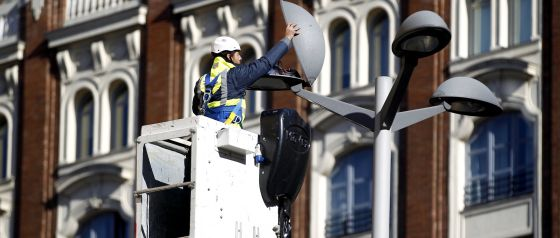 Un operario del ayuntamiento cambia una bombilla de una farola en la Plaza de Callao de Madrid.
